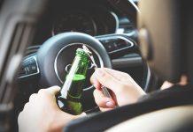 Homme qui décapsule une bière au volant